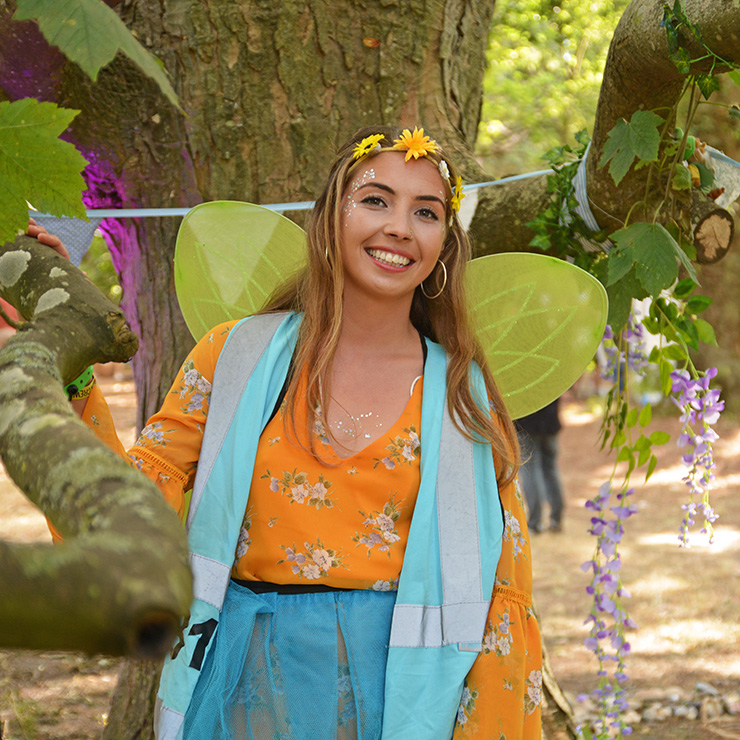 Volunteer at Camp Bestival 2020 with Hotbox Events - Volunteer standing with flowers
